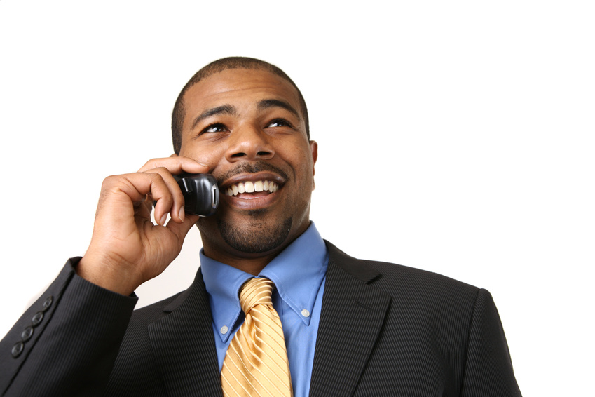 African American businessman talking on mobile phone, smiling. Close-up, isolated over white.